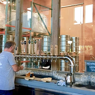 Man pouring a beer from a metal tap
