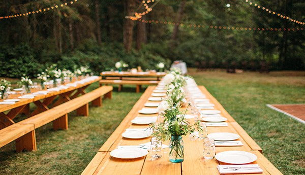 Banquet tables set in a forest clearing