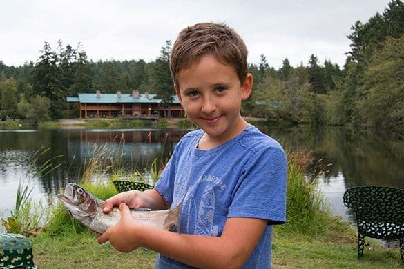 kid with fish and lodge