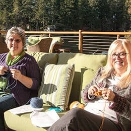 Two women knitting on the deck