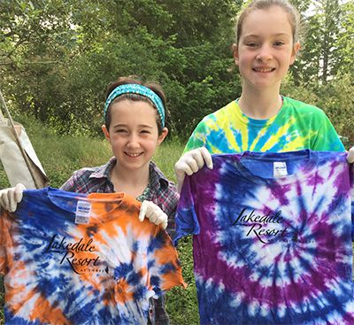 Two girls holding up tie-dyed shirts