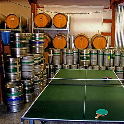 Ping pong table surrounded by kegs of beer