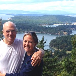 Man and woman standing above a lake and evergreen trees