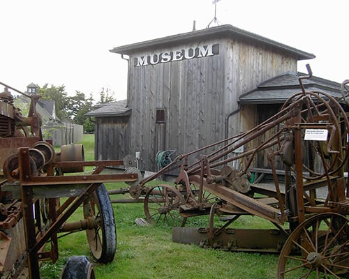 Rusted antique farm equipment in front of a wood building