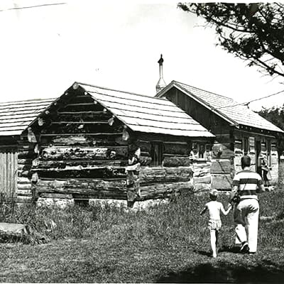 Man and boy walking towards a log cabin