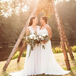 Two brides holding bouquets looking at each other by the lake