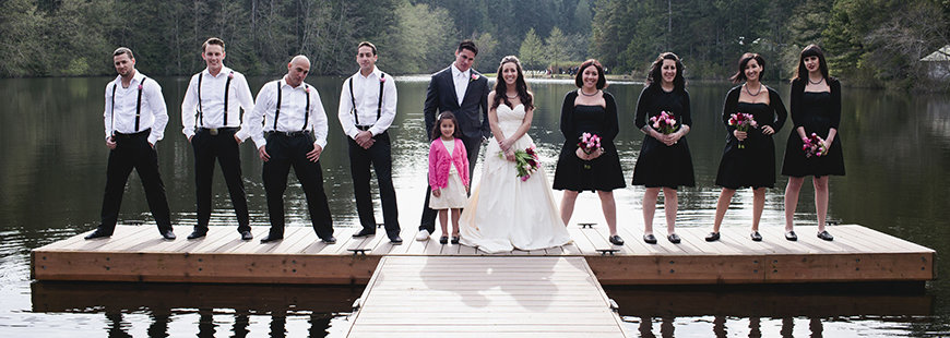 Bride and groom with wedding party standing on dock on the lake