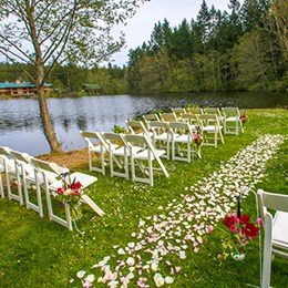 Rose petal strewn aisle between white chairs by the lake