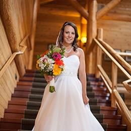 Bride walking down stars in a log cabin