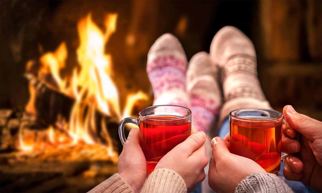 Couple with drinks and cozy socks in front of fire