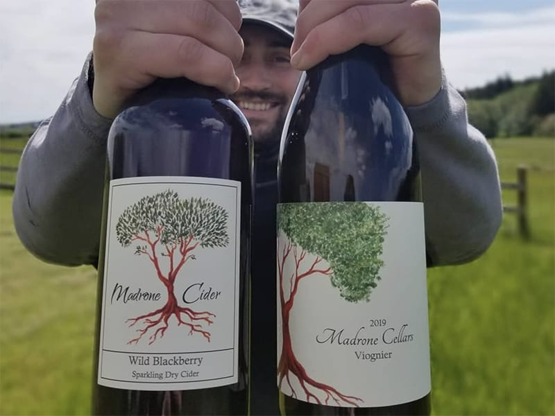 winemaker holding bottles of wine and cider