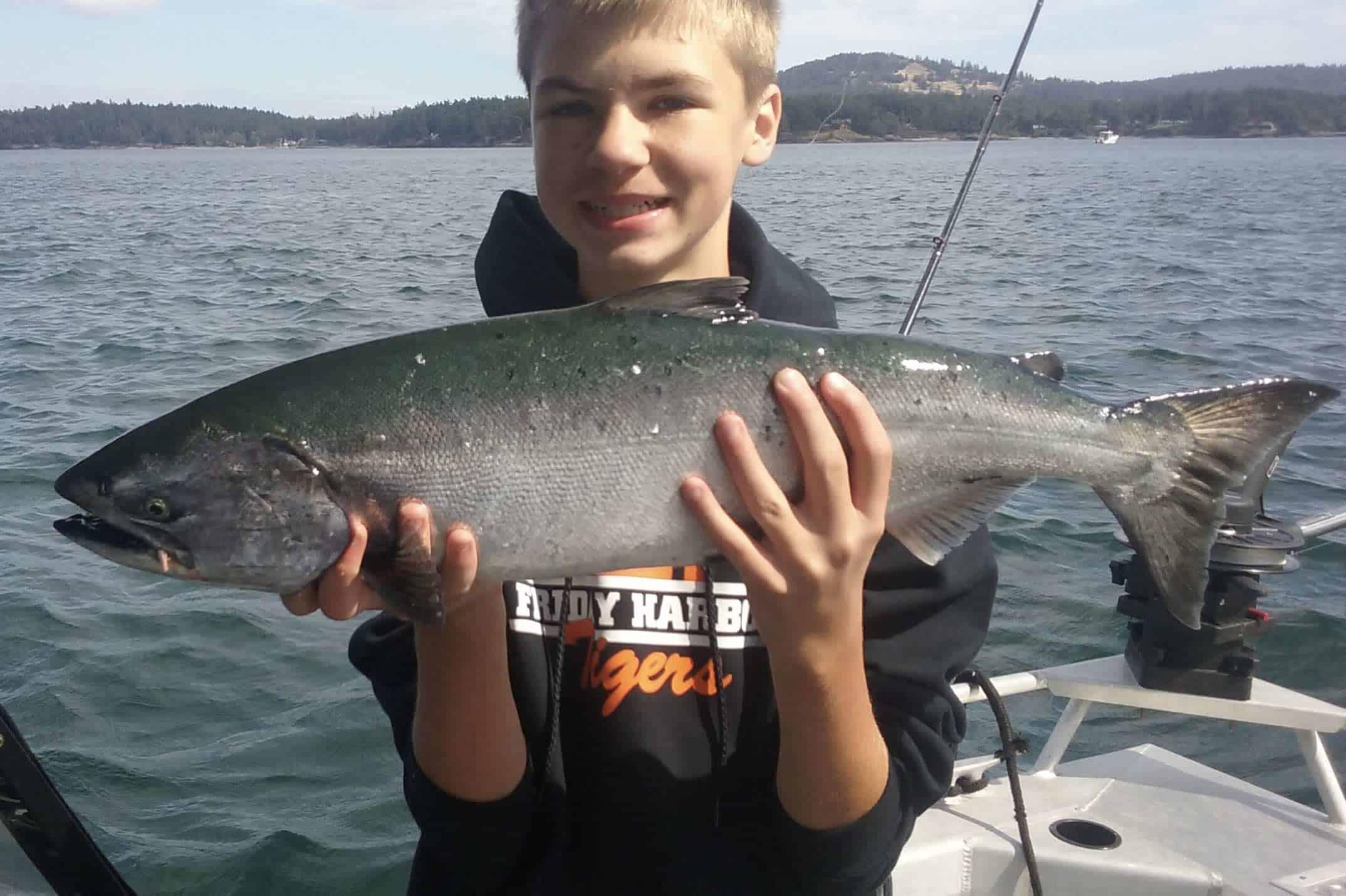boy catching fish on boat rental
