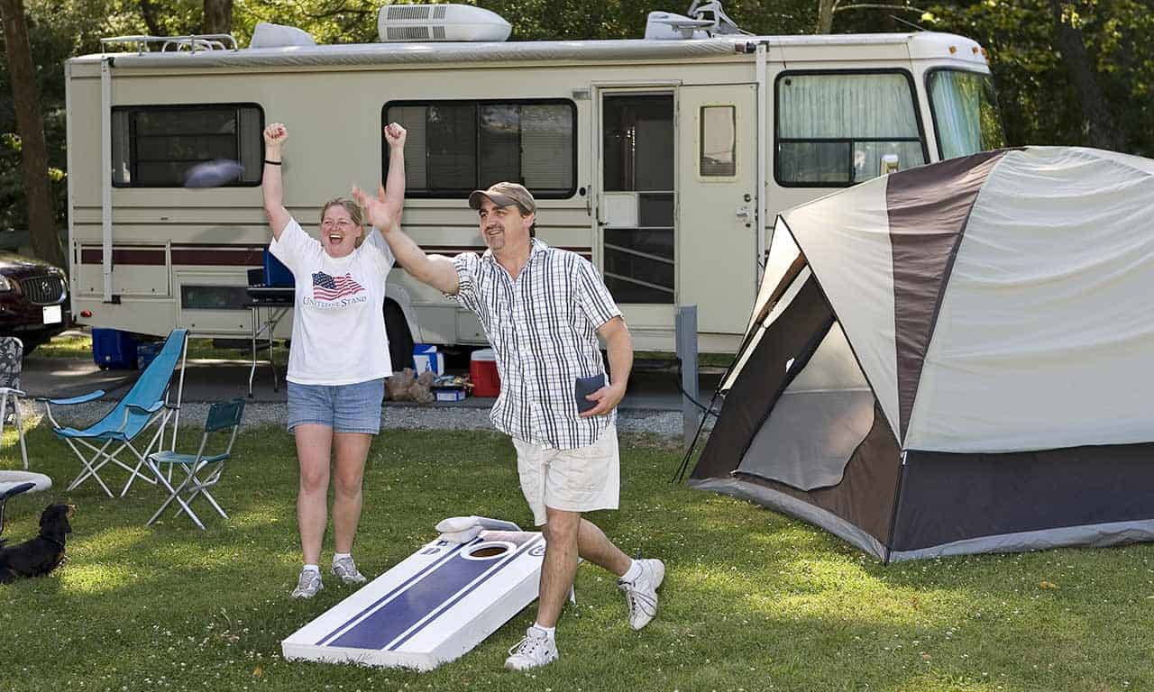 couple-playing-cornhole-with-RV