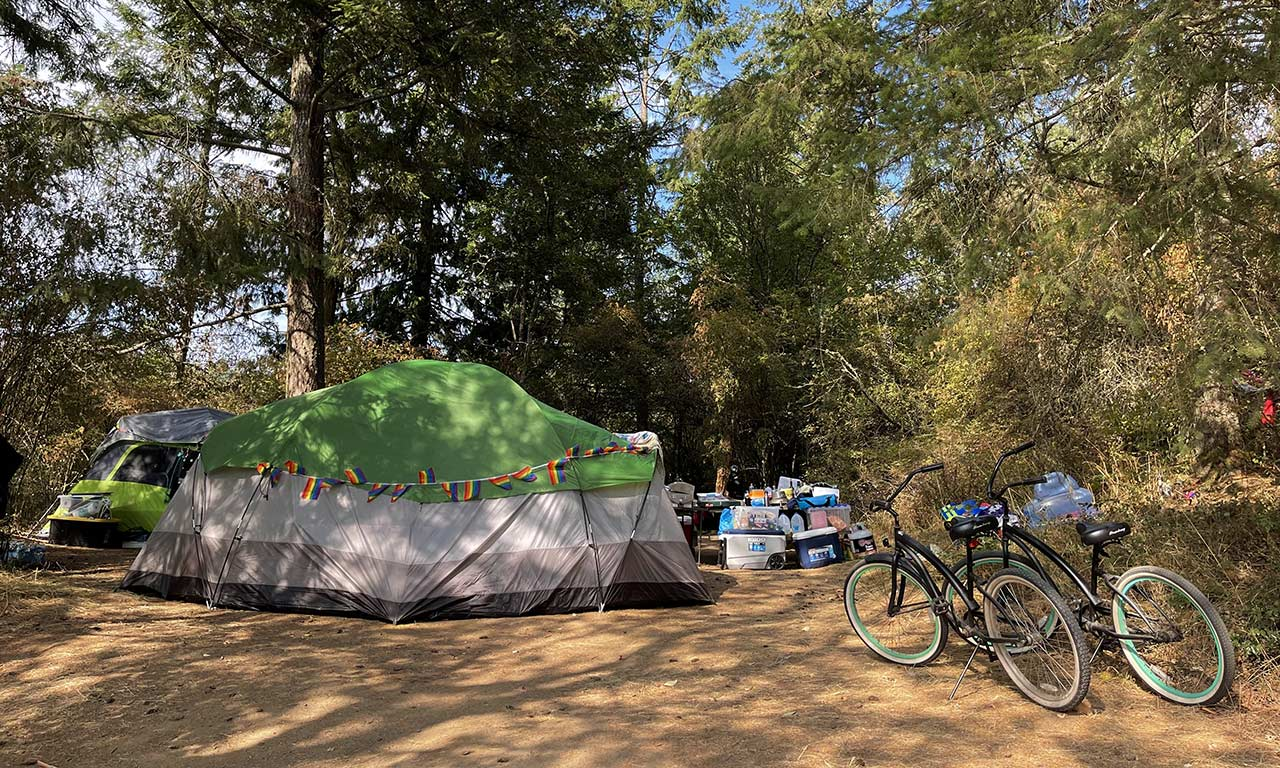 camping-at-Lakedale-with-bikes,-green-tent-and-pride-flags