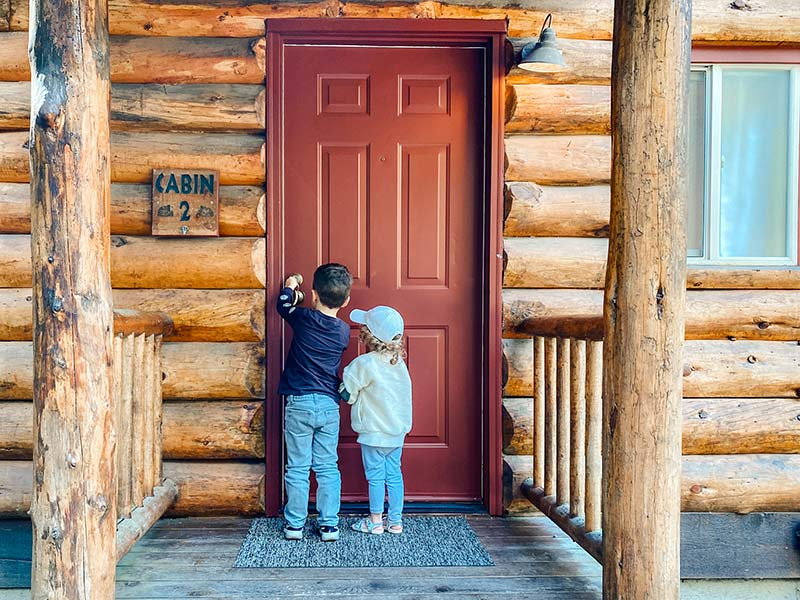 kids at front door of log cabin of Lakedale